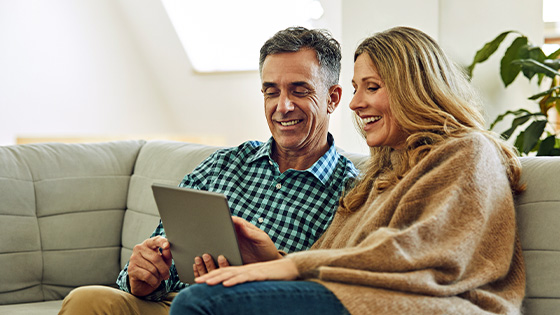 A couple on the couch looking at a tablet