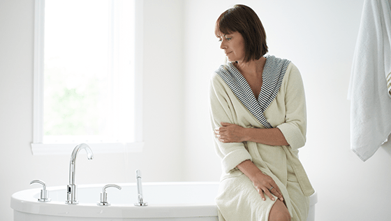 Woman holding her arm while sitting on the edge of a tub