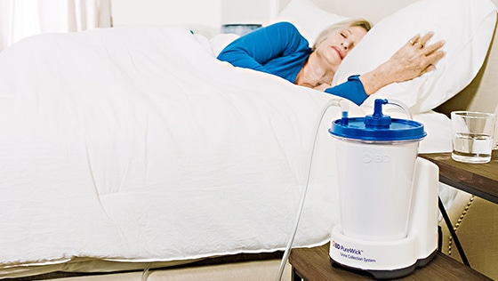 A woman in bed sleep with her Purewick on the night stand