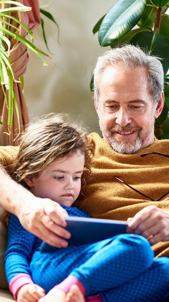 Father reading to daughter from a tablet